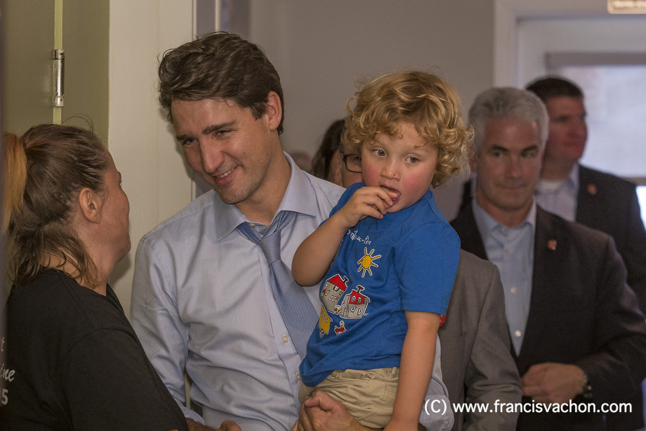 Justin Trudeau shakes hands in a restaurant as he holds his son Hadrien, 3, in Roberval, Qc, on Thursday October 19, 2017. THE CANADIAN PRESS/Francis Vachon.