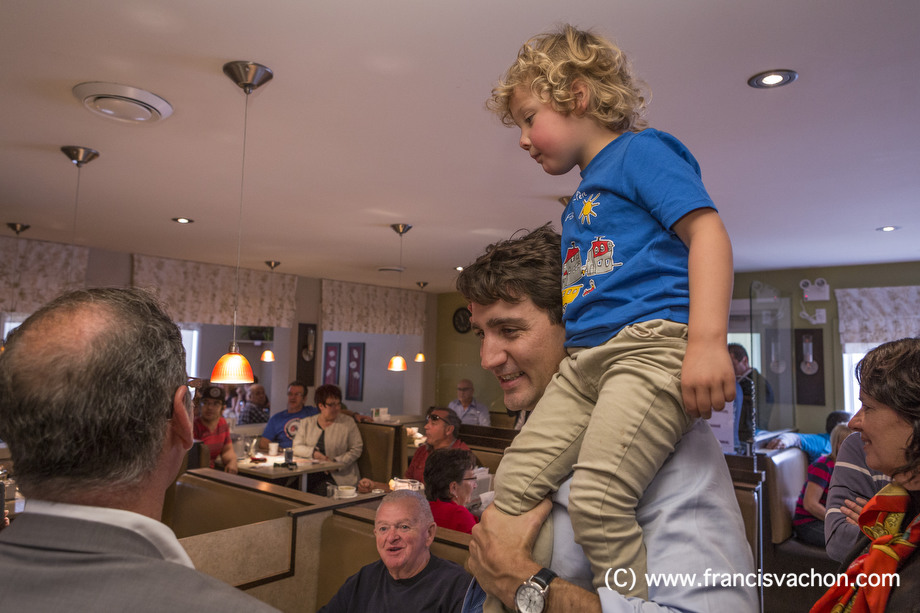 Justin Trudeau shakes hands in a restaurant as his son Hadrien, 3, sits on his shoulder in Roberval, Qc, on Thursday October 19, 2017. THE CANADIAN PRESS/Francis Vachon.