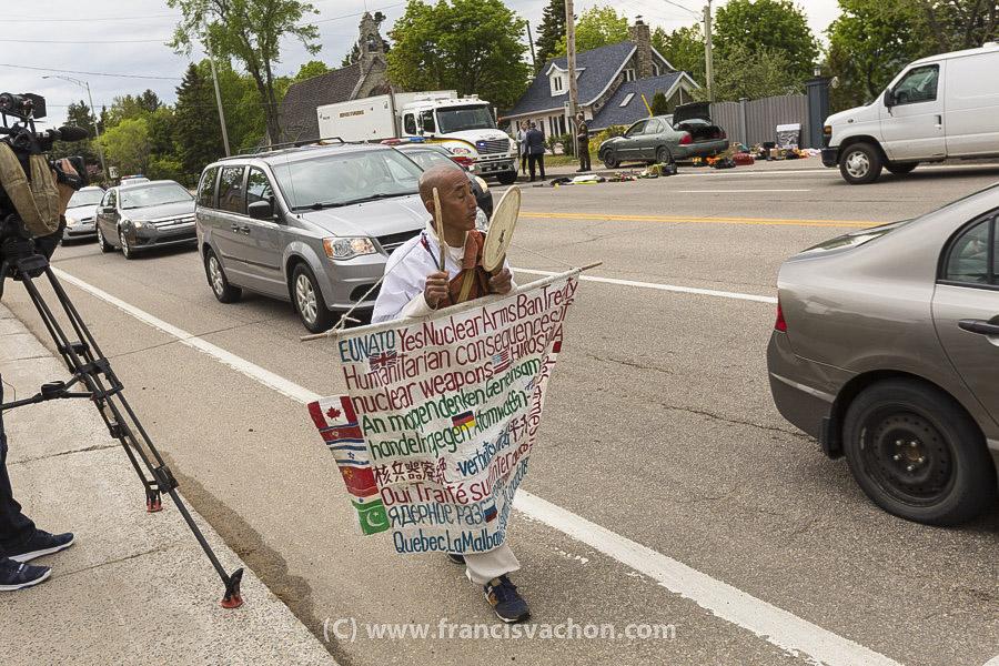 Le manifestant antinucléaire Toyoshige Sekiguchi passe devant un véhicule suspect à La Malbaie après une marche depuis Montréal, le 7 juin 2018.
