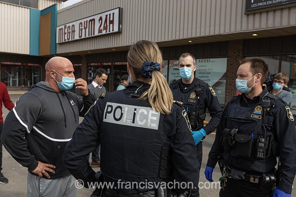 Un entraineur et responsable du Mega Gym 24h discute avec des policiers appelés en assistance de la Sécurité Publique venu remettre un avis de fermeture à Québec le 31 mars 2021.